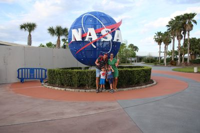 Florida Familienreise - Florida for family - Kennedy Space Center - Familie Albrecht vor NASA Zeichen